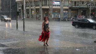 Una mujer con el vestido recogido camina bajo la lluvia en una tormenta por Gran Vía.