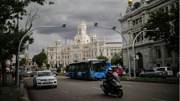 Un autobús entra en la zona que será Madrid Central bajo la atenta mirada de las cámaras y con el Palacio de Cibeles, sede del Ayuntamiento, detrás.