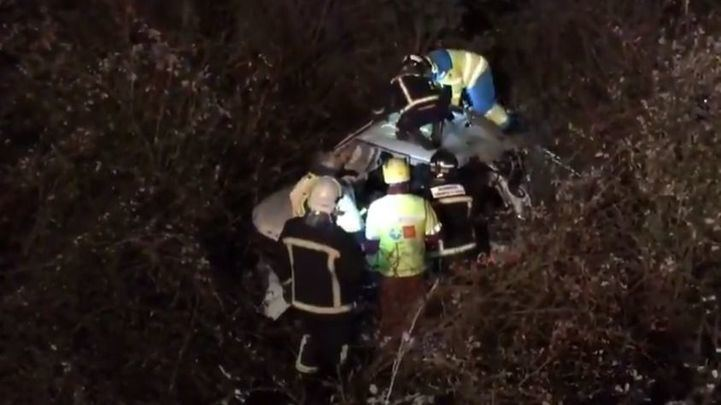 Los bomberos junto al coche accidentado.