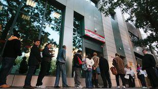 Desempleados esperando a las puertas de una oficina de empleo.