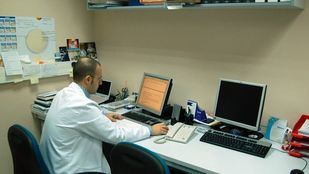 Un médico trabajando ante un ordenador en un laboratorio médico.