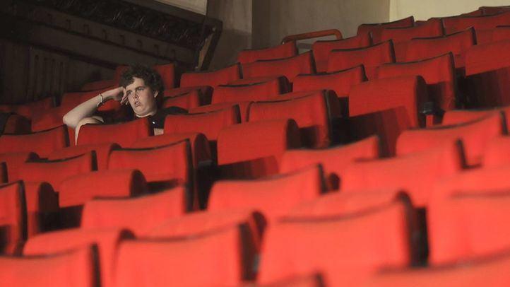 un solitario espectador entre butacas vacias de un cine o teatro