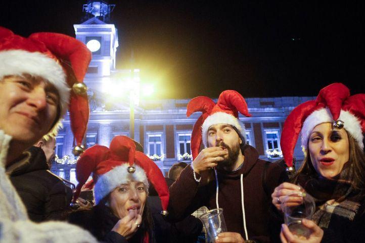 Gente tomando las uvas en la Puerta del Sol.