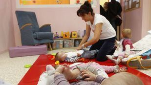 Una monitora cuida de varios bebés en una escuela infantil. Foto de archivo.