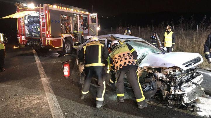 Los bomberos junto al vehículo accidentado.