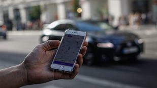 Un usuario de Cabify busca vhículos de transporte con conductor en la Gran Vía.