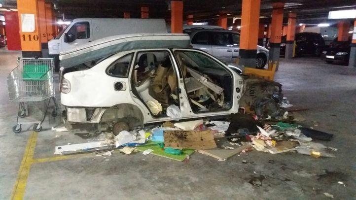 Coche destrozado en el garaje del edificio de viviendas públicas del Ensanche de Vallecas