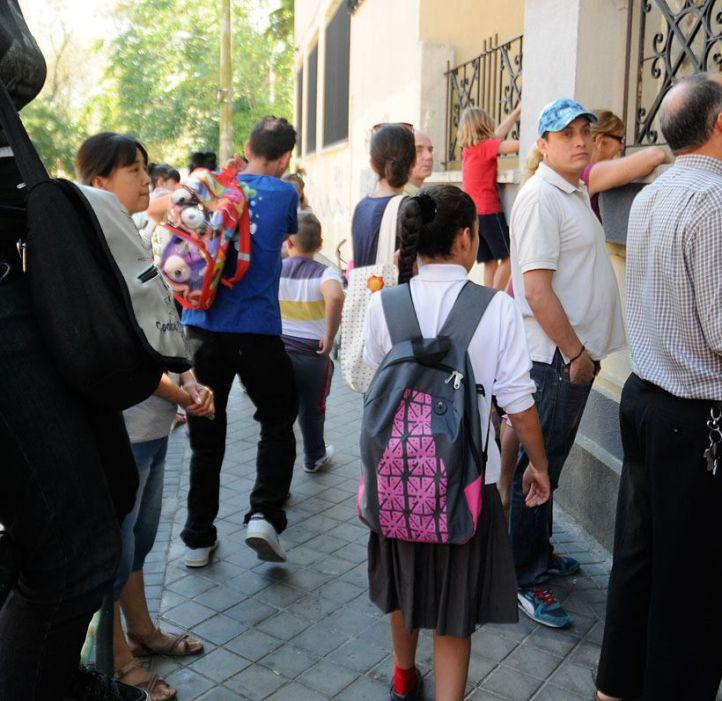niños y padres en la puerta de un colegio de Carabanchel