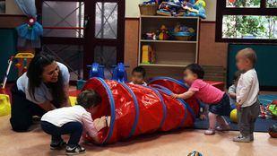 Niños jugando con su cuidadora de la Escuela Infantil El Bosque.