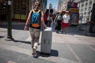 Una turista pasea con una maleta por el centro de Madrid.
