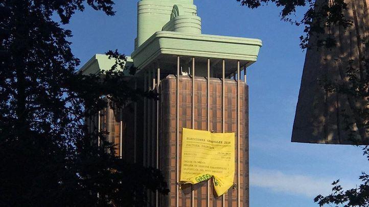 Cuatro escaladores de la organización ecologista han trepado por la fachada de las torres de Colón donde han desplegado una pancarta de cerca de 300 metros cuadrados.