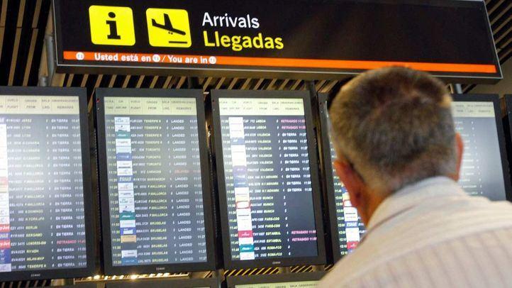 Hombre mirando pantallas de llegadas en el aeropuerto de Barajas