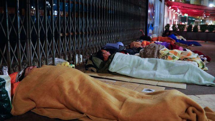 Más de veinte personas duermen a las puertas del teatro cine Real Cinema en la plaza de Isabel II, frente al Teatro Real.