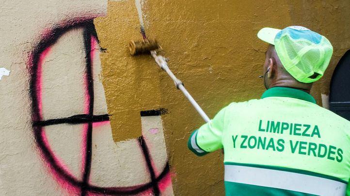 Un barrendero pinta una pared para tapar una pintada.