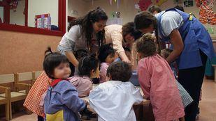Niños jugando con sus cuidadoras de la Escuela Infantil El Bosque.