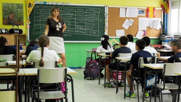 Niños y una profesora dando clase en un colegio.