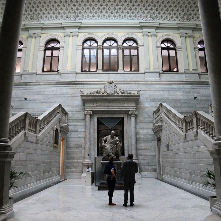 Hall con doble escalinata y estatua dedicada a Menéndez Pelayo en la Biblioteca Nacional.