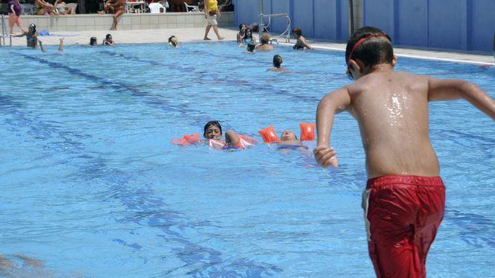 Unos niños con manguitos y otro saltando al agua en la piscina pública San Vicente de Paúl, en una foto de archivo.