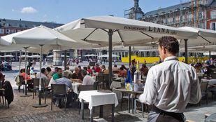 Un camarero atiende a varios turistas en una terraza de la plaza Mayor.