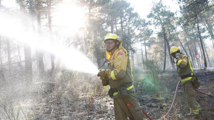 Los bomberos refrescan algunas zonas del terreno afectado.