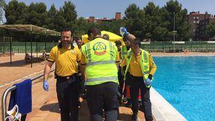 Sanitarios del Samur-Protección Civil atienden a un hombre en la piscina de Orcasitas.