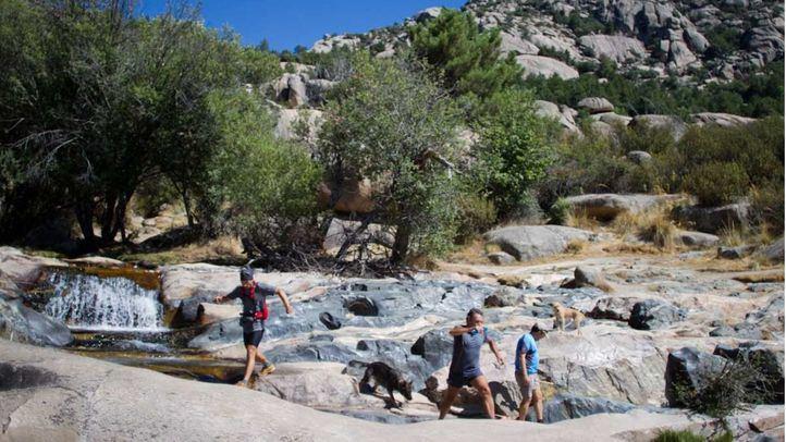 Senderistas saltan las rocas para llegar a la Charca Verde de la Pedriza.