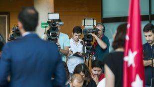 El jefe de prensa de Vox en la Asamblea de Madrid (entre las cámaras) toma notas en directo de la rueda de prensa de Ayuso y Aguado. Como él, miembros de otras formaciones no querían perderse el anuncio del pacto PP-Ciudadanos de primera mano.