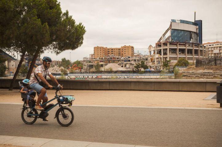 Un ciclista pasea con el estadio Vicente Calderón de fondo.