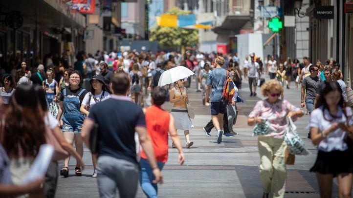 Ciudadanos y turistas, por las céntricas calles de Madrid, donde se concentra un gran número de tiendas.