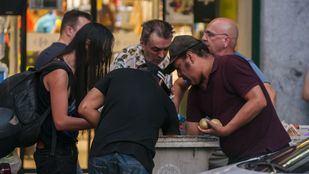 Personas necesitadas buscan comida en los cubos de basura de un centro comercial.