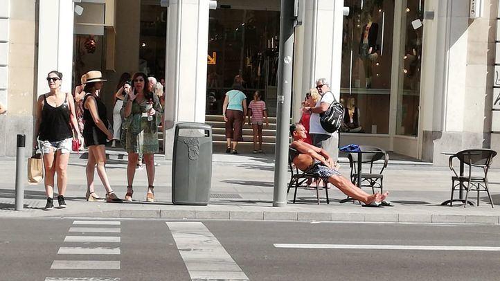 Sin camiseta y en chanclas: así toman el sol los turistas en la Gran Vía
