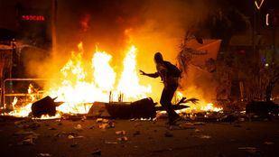Un manifestantes corre frente al fuego durante los disturbios en la Plaza de Urquinaona, en Barcelona.