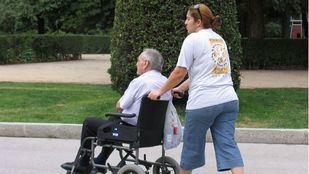Persona mayor en silla de ruedas junto a su cuidadora.