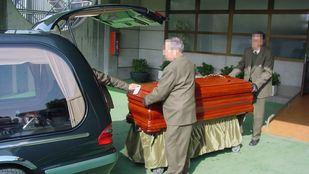 Trabajadores de la empresa mixta de servicios funerarios metiendo un féretro en un coche fúnebre.