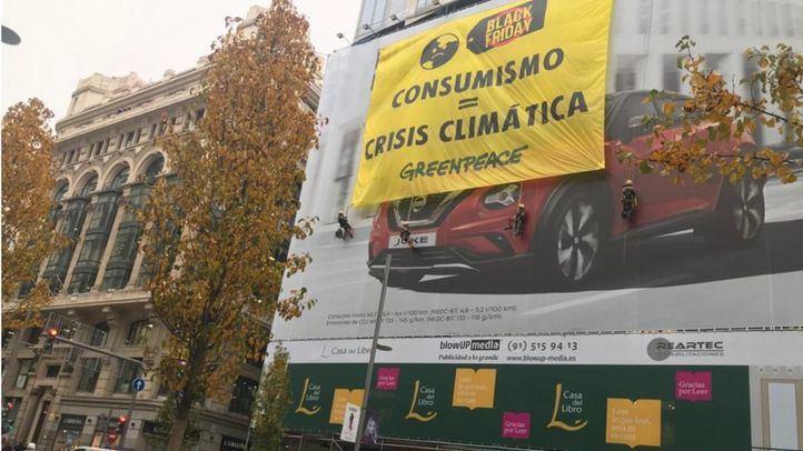 Greenpeace despliega una pancarta contra el consumismo del Black Friday en Gran Vía
