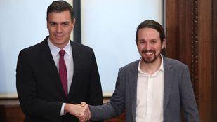 El presidente del Gobierno en funciones, Pedro Sánchez (izq) y el secretario general de Podemos, Pablo Iglesias (dech), se dan la mano durante el acto de presentación del programa de Gobierno del PSOE y Unidas Podemos.