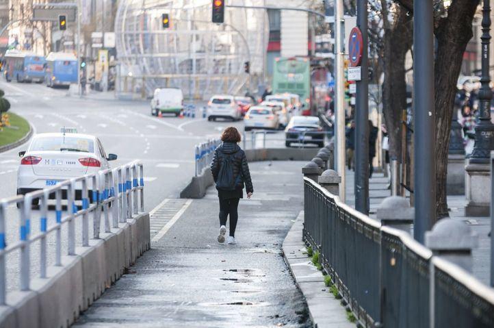 Una mujer camina por el área peatonal de la calle Alcalá entre Cibeles y Barquillo.