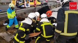 Los bomberos de la Comunidad de Madrid rescatando al hombre atrapado tras el accidente