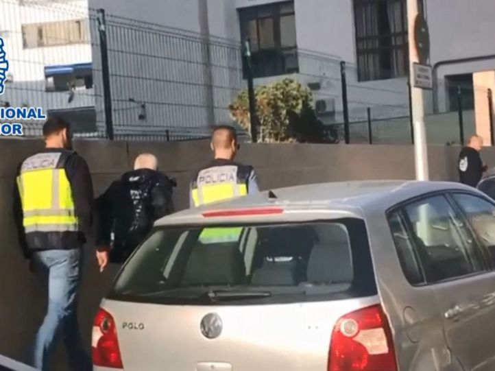 Agentes de la Policía Nacional conduce al detenido que amenazó con atacar la embajada británica en España a dependencias policiales.