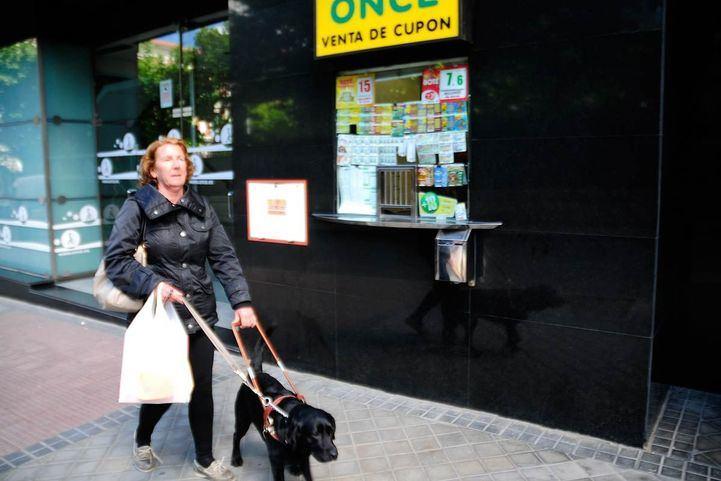 Una mujer invidente con su perro guía pasa por delante de la ONCE