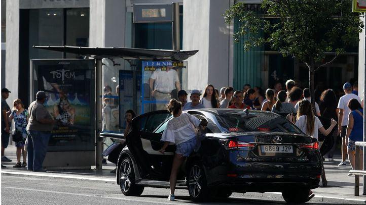 Dos usuariioas de VTC se montan junto a la tienda Mango de la Gran Vía. Foto de archivo