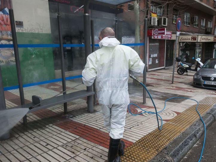 Un operario de limpieza se encarga de desinfectar la marquesina del autobús
