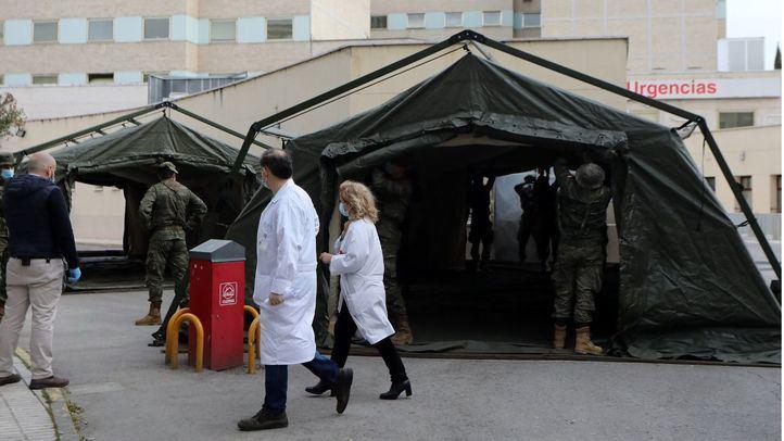 Personal sanitario pasa junto a efectivos del Mando de Ingenieros de Salamanca del Ejército de Tierra, una unidad de 34 militares, mientras instalan un hospital provisional de entre 60 y 70 camas en las inmediaciones del Hospital Gregorio Marañón