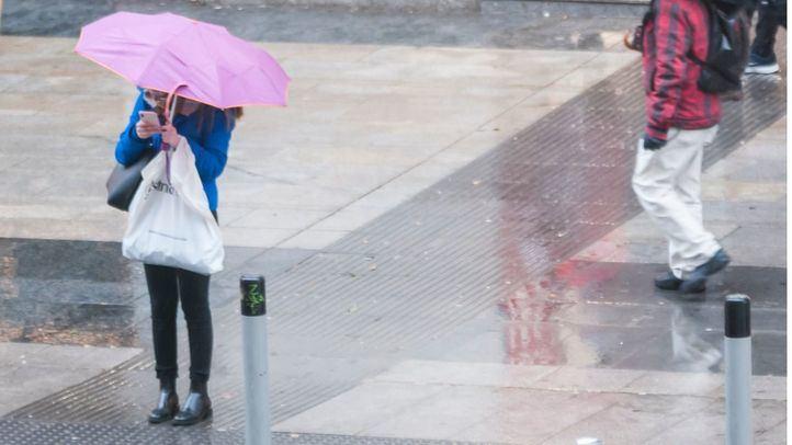 Persona con paraguas en Gran Vía, en una foto de archivo