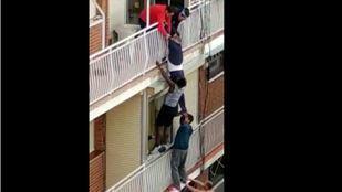 Momento en el que varios vecinos salvan a un hombre de caer al vacío