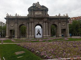 Un lazo negro en la Puerta de Alcalá recuerda a los fallecidos por COVID-19