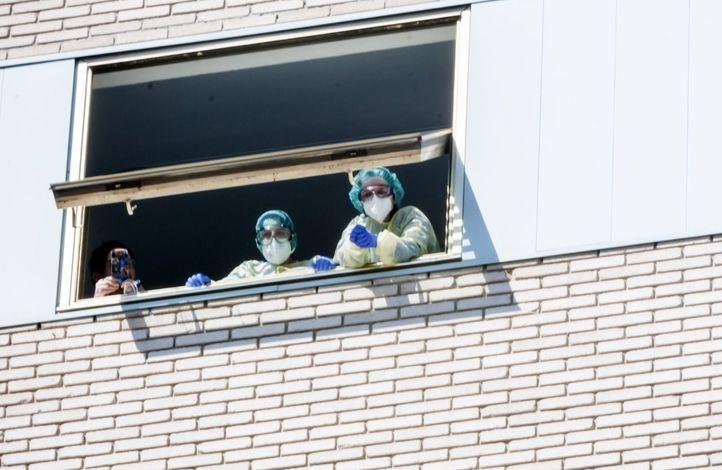 Unos enfermos desde la ventana del hospital.