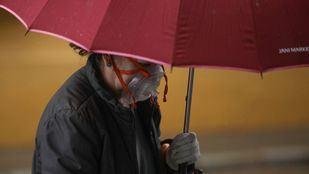 Mujer bajo la lluvia con mascarilla
