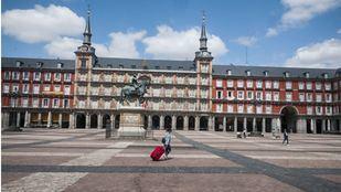 Mujer con una maleta cruzando una Plaza Mayor desierta