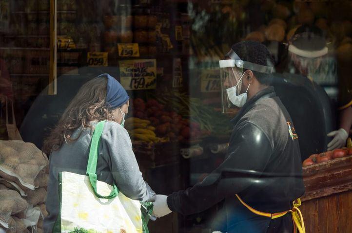 Un trabajador de un supermercado, protegido contra el Covid-19, trabaja para permitir la distribución de aliementos durante la pandemia